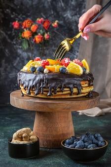 Вкусный шоколадный торт со свежими фруктами на темной стене, вид спереди