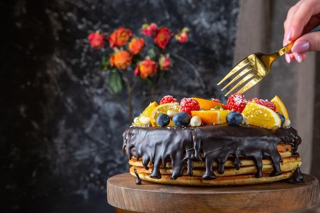 어두운 벽에 신선한 과일과 함께 전면보기 맛있는 초콜릿 케이크