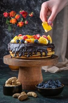 暗い壁に新鮮な果物と正面図おいしいチョコレートケーキ