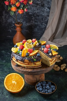 Front view yummy chocolate cake with fruits on dark wall