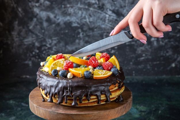 Front view yummy chocolate cake with fruits getting cut by female on dark wall