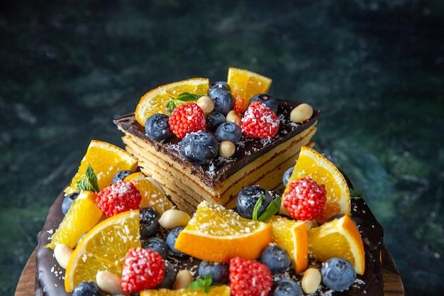Вкусный шоколадный торт с фруктами на темной стене, вид спереди