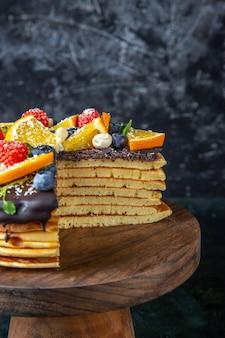 어두운 벽에 과일과 함께 전면보기 맛있는 초콜릿 케이크
