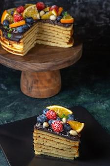 暗い壁に果物と正面図おいしいチョコレートケーキ