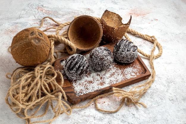 Вид спереди вкусные шоколадные торты с кокосом на светло-белой поверхности выпечка бисквитный сахарный торт сладкое печенье шоколад