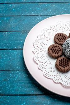 Biscotti al cioccolato squisiti di vista frontale con torta al cioccolato sul biscotto dolce del biscotto del tè del cacao della torta rustica blu dello scrittorio
