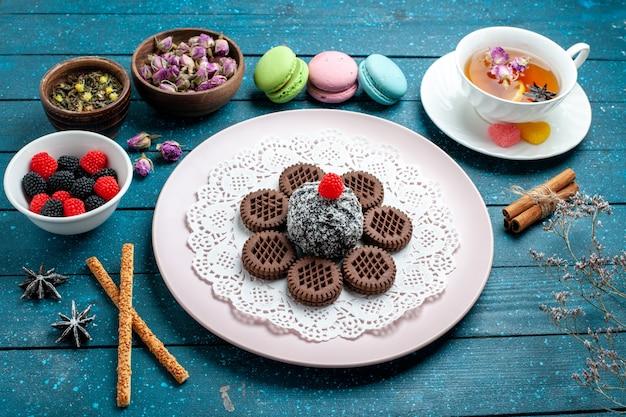 青い素朴なデスクケーキココアティー甘いビスケットクッキーにコンフィチュールとお茶を添えた正面図おいしいチョコレートクッキー