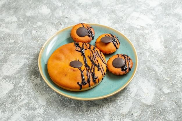 正面図白い背景の上のプレートの内側にチョコレートのアイシングとおいしいココアケーキ甘いケーキビスケットデザートクッキーパイ