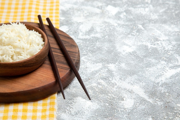 Front view yummy cooked rice inside brown plate on white space