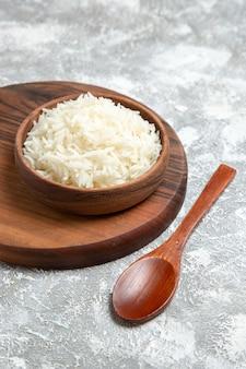 Vista frontale gustoso riso cotto all'interno del piatto sulla scrivania bianca