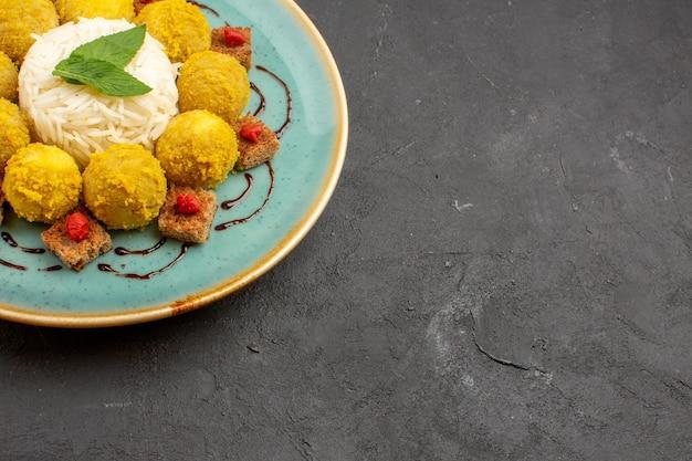 暗い机の上の皿の中にミートボールを入れたおいしい炊き込みご飯の正面図