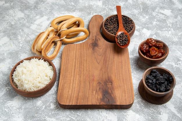 Вкусный приготовленный рис с приправами и сладкими крекерами на белом фоне, вид спереди