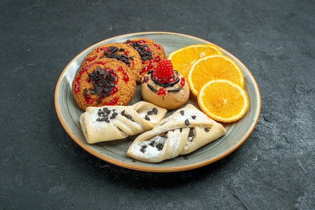 フルーティーなペストリーと暗い表面にオレンジのスライスが付いた正面図のおいしいクッキーフルーツスイートケーキパイティーシュガー