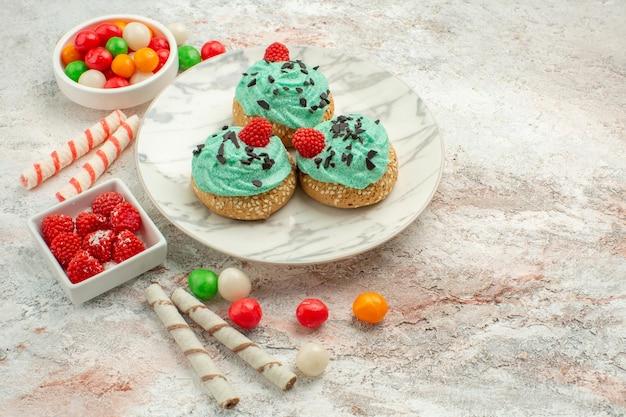 白い背景の上のカラフルなキャンディーと正面図おいしいクリームケーキビスケット甘いデザートクリーム