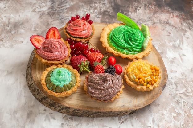 ライトテーブルのデザートビスケットの甘いケーキにフルーツと正面図おいしいクリームケーキ