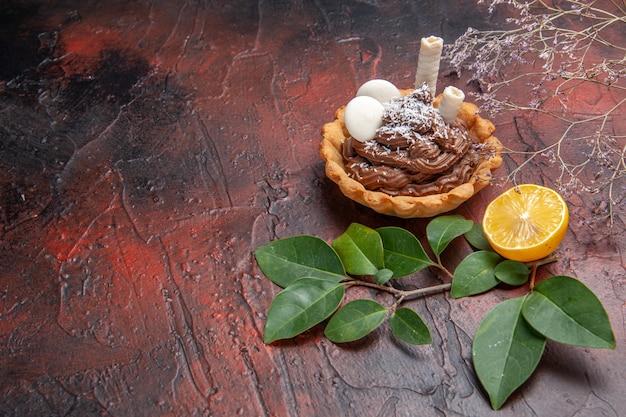 正面図ダークテーブルケーキビスケットデザートスウィートのおいしいクリーミーなケーキ