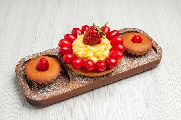 正面図白い机の上のケーキとおいしいクリーミーなケーキビスケットケーキクッキーティー