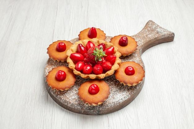 Torta cremosa squisita di vista frontale con le torte sul biscotto della torta del biscotto del tè dello scrittorio bianco