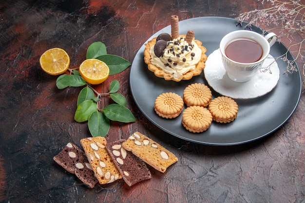 Вкусный сливочный торт с чаем на темном столе, сладкий торт, десерт, вид спереди