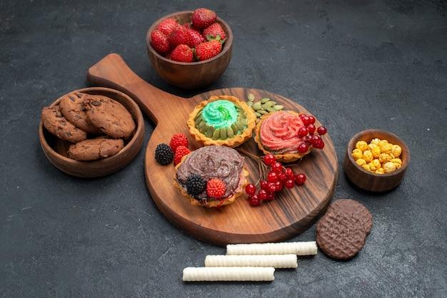 ダークテーブルのビスケットデザートクッキーにベリーとおいしいクリーミーなケーキの正面図