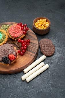 正面図ダークテーブルクッキービスケットデザートにベリーとおいしいクリーミーなケーキ