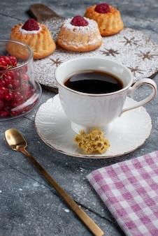 グレーのデスクビスケット甘いフルーツのコーヒーと新鮮な赤いクランベリーのカップと正面のおいしいdケーキ