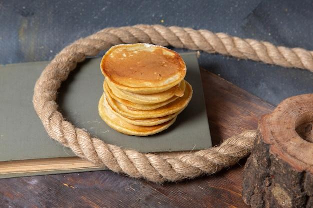 Vista frontale yummy deliziosi muffin con corde sullo sfondo grigio cibo pasto colazione frittelle dolci