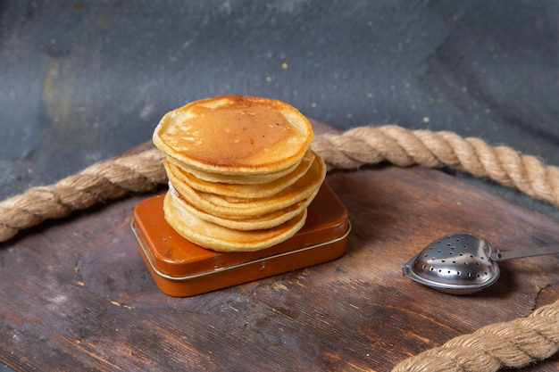Front view yummy delicious pancakes on the wooden desk with ropes on the grey background food meal breakfast sweet muffin
