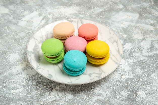 Вид спереди вкусные французские макароны красочные пирожные внутри тарелки на белой поверхности торт сахарный бисквит сладкий пирог печенье