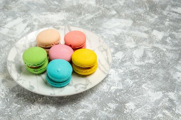 Вид спереди вкусные французские макароны красочные пирожные внутри тарелки на белой поверхности торт сахарное печенье сладкий пирог печенье