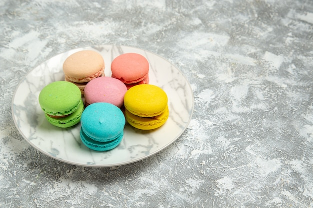 Front view yummy french macarons colorful cakes inside plate on white surface cake sugar biscuit sweet pie cookie