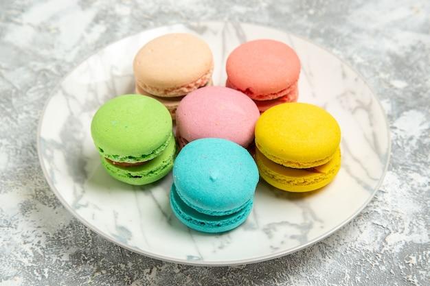 Vista frontale yummy macarons francesi torte colorate all'interno della piastra sulla superficie bianca torta zucchero biscotto torta dolce biscotti