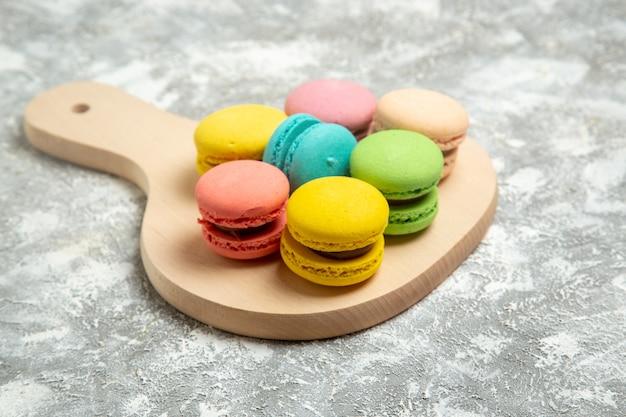 Вид спереди вкусные французские макароны красочные пирожные на белой поверхности торт пирог сахарное печенье сладкое печенье