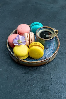 Front view yummy french macarons with coffee on dark space