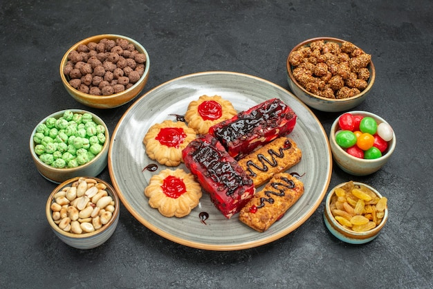 어두운 공간에 쿠키와 사탕이있는 전면보기 맛있는 과일 케이크