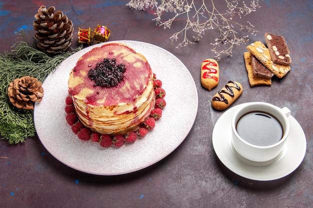 Vista frontale gustosi pancake fruttati con una tazza di tè su uno spazio buio
