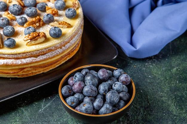 プレートの暗い表面の中にブルーベリーとクルミが入った正面図のおいしいハニーケーキ
