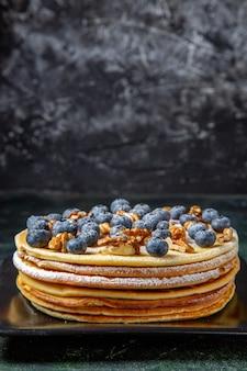 블루 베리와 호두 플레이트 어두운 표면 안에 전면보기 맛있는 꿀 케이크