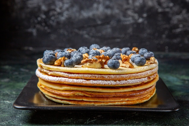 Front view yummy honey cake with blueberries and walnuts inside plate dark surface