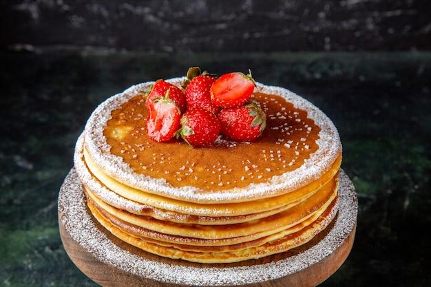 丸い木の板の暗い表面に新鮮なイチゴと正面図おいしい蜂蜜ケーキ