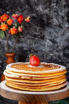 둥근 나무 보드 어두운 표면에 설탕 가루와 전면보기 맛있는 꿀 케이크