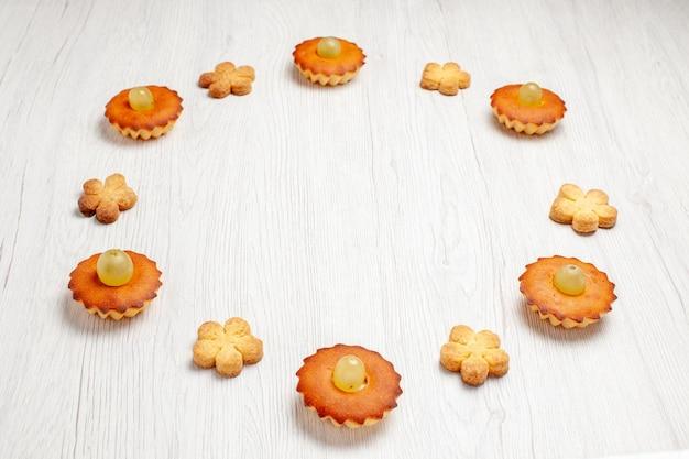 전면 보기 흰색 배경에 쿠키가 늘어선 맛있는 작은 케이크 디저트 비스킷 차 케이크 파이 달콤한 쿠키
