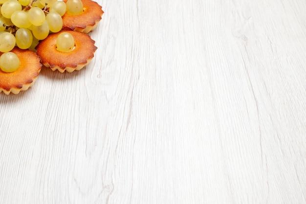 正面図白い机の上にブドウが並ぶおいしい小さなケーキティーケーキパイ甘いデザートクッキー