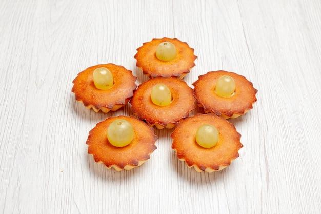 Vista frontale deliziose piccole torte dolci perfetti per il tè allineati su una scrivania bianca torta torta dolce dessert tè biscotto