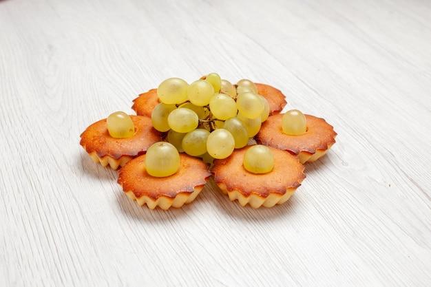 Vista frontale deliziose piccole torte dolci perfetti per il tè allineati con l'uva su una torta da scrivania bianca torta dolce da dessert biscotti da tè
