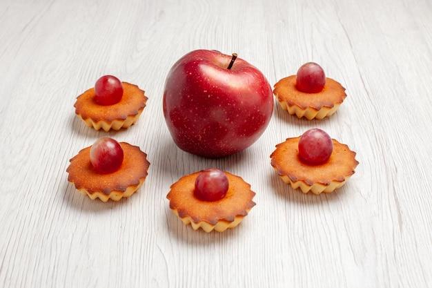 正面図白い背景の上のリンゴとおいしい小さなケーキデザートビスケットティーケーキパイクッキー