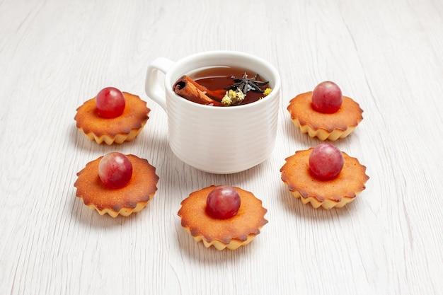 正面図白い背景の上のお茶とおいしい小さなケーキデザートビスケットティーケーキパイクッキー