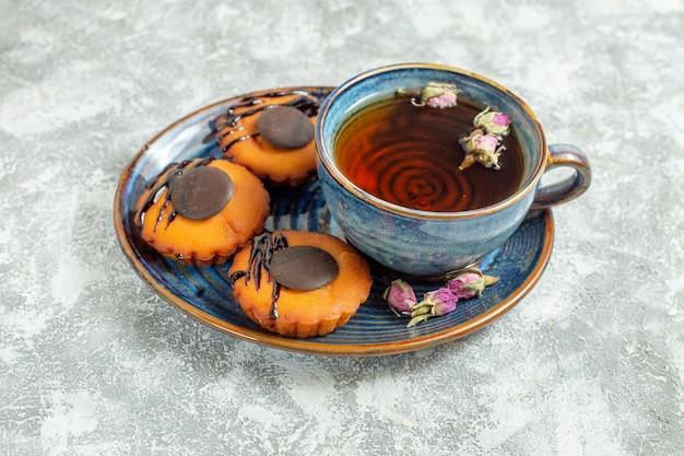 正面図白い背景の上のお茶とおいしい小さなケーキケーキビスケットクッキーデザート茶甘い