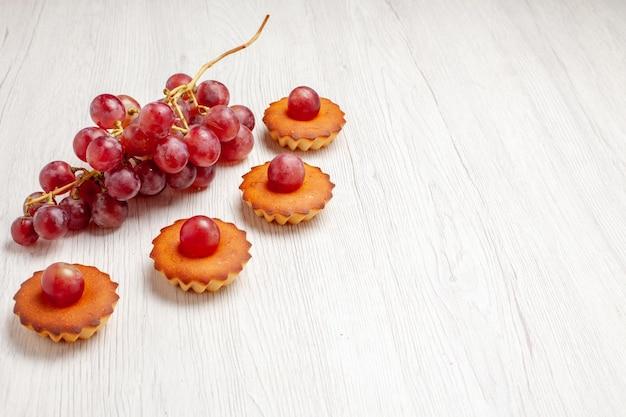 Вид спереди вкусные маленькие пирожные со свежим виноградом на белом фоне фруктовый чай десертное печенье бисквитный торт пирог