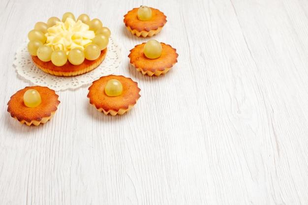 正面図白い背景の上の緑のブドウとおいしい小さなケーキフルーツティーデザートクッキービスケットケーキパイ
